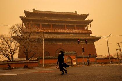 Una mujer pasa por Drum Tower durante la hora punta de la mañana como Beijing, Chin. REUTERS/Thomas Peter