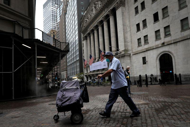 Un trabajador del Servicio Postal pasa con un carrito frente al edificio de la Bolsa de Nueva York, EEUU. 26 octubre 2020. REUTERS/Mike Segar