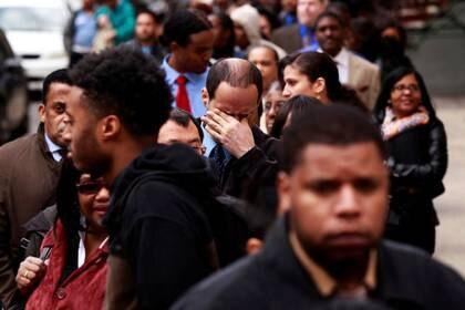 FOTO DE ARCHIVO. Un hombre se frota los ojos mientras espera en una fila de solicitantes de empleo para asistir a una feria de empleo en Nueva York, EEUU. 12 de abril de 2012. REUTERS/Lucas Jackson.