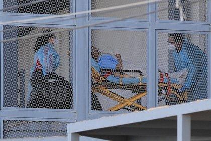 Paramédicos ingresan a un adulto enfermo de Covid-19 al área especializada, en el Hospital General de Ciudad Juárez (México). EFE/ Luis Torres