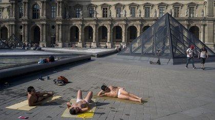 En París y otras ciudades europeas, las fuentes se llenan de gente que busca refrescarse (AP)
