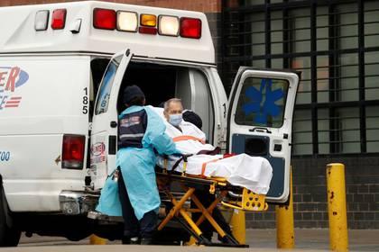 Paramédicos subiendo a un paciente a una ambulancia afuera del Elmhurst Hospital Center, durante la pandemia del COVID-19, la enfermedad causada por el coronavirus, en el distrito de Queens  (Reuters)