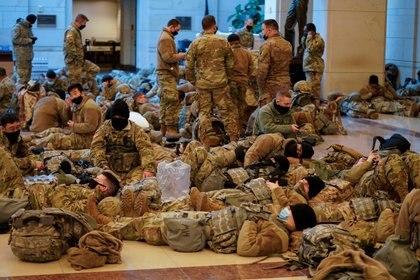 Miembros de la Guardia Nacional descansan en el Capitolio la noche anterior del debate por el Juicio Político al presidente Donald Trump (REUTERS/Joshua Roberts)