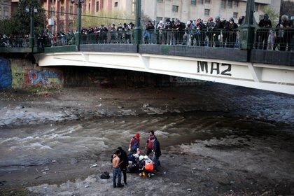 Un grupo de personas asistió al manifestante que cayó al río Mapocho durante la protesta en Santiago de Chile (AILEN DÍAZ / AILEN DÍAZ/AGENCIAUNO)