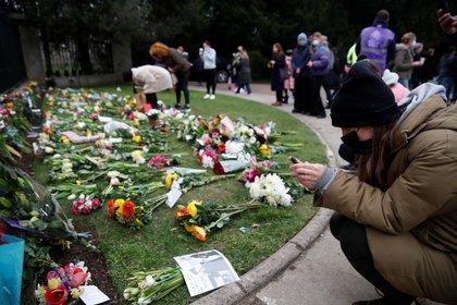 Varias personas depositan flores al exterior del Castillo de Windsor tras la muerte del príncipe Felipe, en Windsor, cerca de Londres, Reino Unido. 10 abril 2021. REUTERS/Andrew Boyers