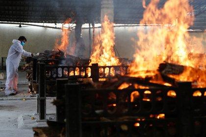 Un trabajador de primera línea enciende una pira funeraria de un paciente con enfermedad por coronavirus (COVID-19) que falleció después de que un hospital se incendiara, en Virar, en las afueras de Mumbai, India, el 23 de abril de 2021. REUTERS / Francis Mascarenhas