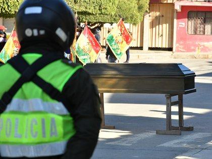 BOL35 TIQUIPAYA (BOLIVIA) 06/07/2020.- Un grupo de vecinos lleva un ataúd vacío ante la Alcaldía, este lunes en Tiquipaya (Bolivia). Estos vecinos reclaman un centro de aislamiento para prevenir contagios por la COVID-19 en la localidad boliviana de Tiquipaya y más fosas en el cementerio para fallecidos por el nuevo coronavirus, para evitar un colapso en el camposanto. EFE/Jorge Ábrego