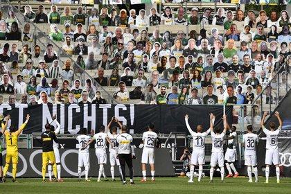 Los jugadores del Borussia Moenchengladbach celebran frente a fotos de sus hinchas colocadas en su estadio sin público, en el regreso de la Bundesliga después de la suspensión por la pandemia (31 de mayo)