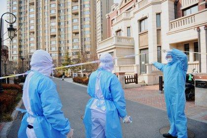 Varios trabajadores visitan a una familia en cuarentena en Qingdao, provincia de Shandong, China. EFE/EPA/YU FANGPING/Archivo