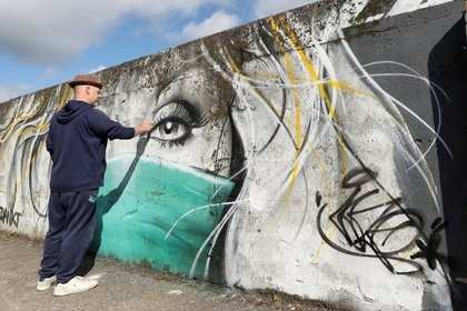 El artista belga CAZ retoca su mural en apoyo a los trabajadores de salud en Wetteren, Belgium.