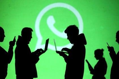 Imagen de archivo ilustrativa de siluetas de usuarios de teléfonos móviles y laptops frente a una pantalla que proyecta el logo de Whatsapp, que ya es la segunda mayor red social a nivel mundial (Foto: Reuters/Dado Ruvic/Ilustración/Archivo)