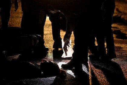 Un agente coloca una pistola dentro de una bolsa en una escena del crimen en Manila, donde la policía dice que disparó a dos hombres que se apresuraron desde un puesto de control. Los sospechosos de drogas casi nunca sobreviven a encuentros violentos con la policía de Filipinas, según una investigación de Reuters (Reuters)