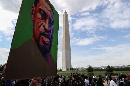 """Un cartel con el rostro de George Floyd, que murió bajo custodia de la policía de Minneapolis, es sostenido por un manifestante que participó en la marcha """"Quita la rodilla de nuestros cuellos"""" junto al Monumento a Washington el 28 de agosto de 2020 (REUTERS/Leah Millis)"""