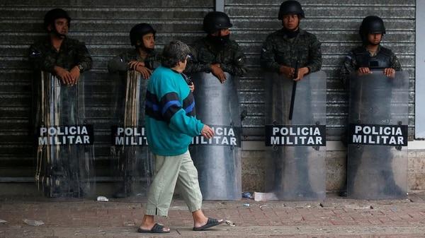 Una mujer camina frente a policías en Tegucigalpa (Reuters)