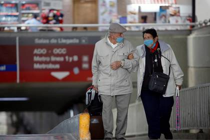 An elderly couple wearing protective masks arrives at the TAPO bus terminal after Mexico registered its first death from the coronavirus disease (COVID-19), in Mexico City, Mexico March 19, 2020. REUTERS/Gustavo Graf