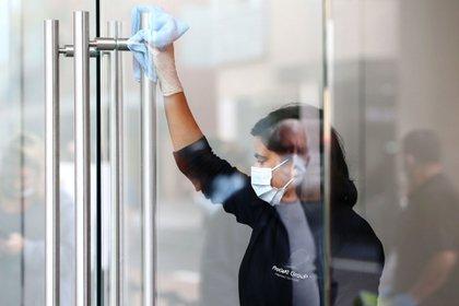 Un trabajador con una máscara protectora higieniza las manijas de las puertas de una tienda de Apple en el suburbio de Bondi Junction de Sydney