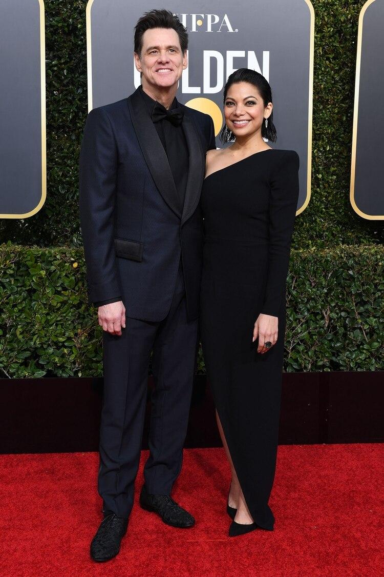 Jim Carrey presentó en la red carpet de los Golden Globes como novia oficial a Ginger Gonzaga. Él eligió un esmoquin bicolor en azul y negro. ¿El detalle fashion? Sus zapatos tramados de animal print. Ella lo acompañó con un vestido asimétrico negro y stilettos en punta a tono
