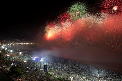 La gente observa cómo los fuegos artificiales explotan en la playa de Copacabana durante las celebraciones de Año Nuevo en Río de Janeiro, Brasil, el 1 de enero de 2020. (REUTERS / Ueslei Marcelino)