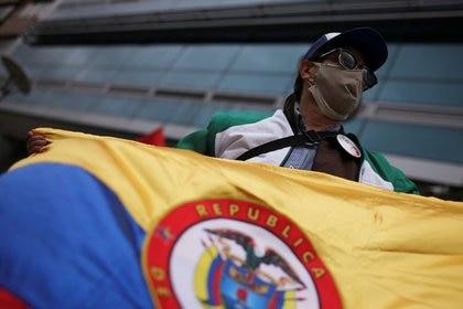 Un hombre utilizando una mascarilla sostiene una bandera en medio de manifestaciones en Bogotá, Colombia. Septiembre 7 de 2020. REUTERS/Luisa González