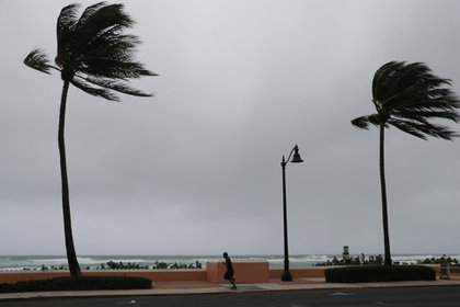 PALM BEACH, FLORIDA - AUGUST 02: A runner is seen as Tropical Storm Isaias passes through the area on August 02, 2020 in Deerfield Beach, Florida. The storm is brushing along the east coast of Florida and tropical storm conditions will extend northward along the coasts of Georgia and South Carolina. Joe Raedle/Getty Images/AFP