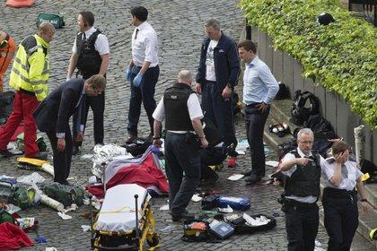 El ministro conservador observa el cuerpo cubierto del policía atacado por el terrorista (Stefan Rousseau/PA via AP).