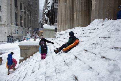 Personas juegan con la nieve frente al edificio de la bolsa de Wall Street. (Kena Betancur / AFP)