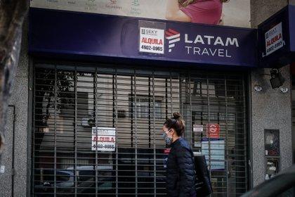 Una mujer fue registrada este miércoles al caminar frente a un local cerrado de la aerolínea chilena Latam, en Buenos Aires (Argentina). EFE/Juan Ignacio Roncoroni