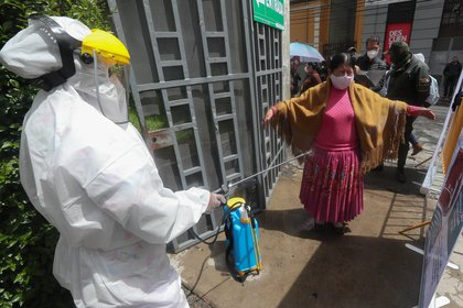 A member of the Departmental Health System disinfects a woman at the entrance to the Julio Borelli Coliseum in La Paz (Bolivia). EFE / Martín Alipaz / Archive