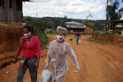 """Vanderlecia Ortega dos Santos, una enfermera de la tribu Witoto, que se ofreció como voluntaria para brindar la única atención de primera línea que protege a su comunidad indígena de 700 familias del brote de COVID-19, y la profesora de idiomas y artesana Natalina Martins Ricardo , use máscaras protectoras que dicen """"Las vidas indígenas importan"""", mientras caminan por una carretera en el Parque das Trios en el distrito de Taruma, Manaus (REUTERS / Bruno Kelly )"""