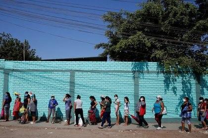 Mujeres utilizando mascarillas hacen fila para ingresar a un mercado en Lima, cuando aún regía los días alternados por género para salir a la vía pública