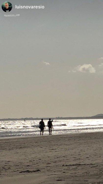 El periodista y su pareja, caminando por la playa (Instagram)