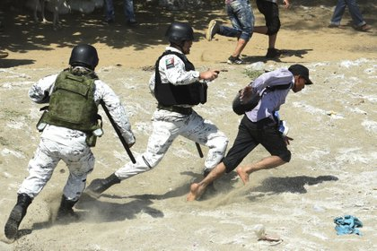 Un elemento de la Guardia Nacional patea a un migrante que cruzó por el Río Suchiate. (Foto: ISAAC GUZMAN / AFP)