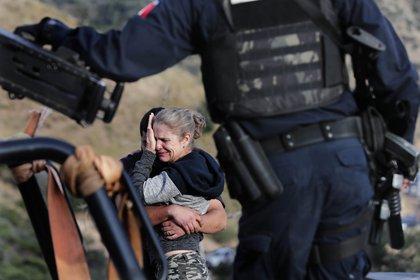 Custodiados por las fuerzas de seguridad mexicanas, miembros de la familia LeBarón lloran a sus muertos en el lugar donde nueve ciudadanos estadounidenses _ tres mujeres y seis niños _ fueron asesinados en una emboscada de un cártel, cerca de Bavispe, en la frontera entre los estados de Sonora y Chihuahua, México, el 6 de noviembre de 2019. (AP Foto/Marco Ugarte)