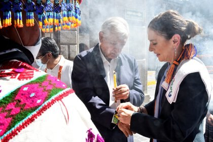 Mexican President Andres Manuel Lopez Obrador holds a candle as his wife Beatriz Gutierrez puts him a bracelet during the opening of an altar in memory of the victims of the coronavirus disease (COVID-19), at the National Palace in Mexico City, Mexico October 31, 2020. Mexico's Presidency/Handout via REUTERS ATTENTION EDITORS - THIS IMAGE HAS BEEN SUPPLIED BY A THIRD PARTY. NO RESALES. NO ARCHIVES