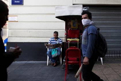 A shoe shiner reads the paper as he waits for costumers in one of the main streets in downtown as Mexico's government declared a health emergency and issued stricter rules to curb the spread of the coronavirus disease (COVID-19), in Mexico City, Mexico April 3, 2020. REUTERS/Carlos Jasso