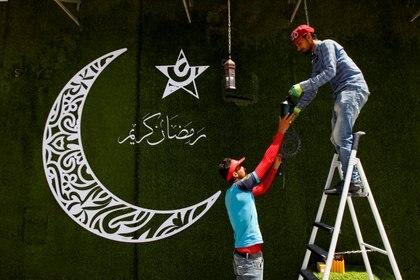 """Los trabajadores cuelgan linternas tradicionales de Ramadán, llamadas """"fanous"""", como parte de los preparativos antes del mes sagrado de ayuno del Ramadán, en Najaf, Irak, el 12 de abril de 2021. REUTERS / Alaa Al-Marjani"""