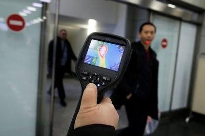 Trabajadores del servicio de epidemiología de Kazajistán utilizan un escáner térmico para detectar viajeros de China que pueden tener síntomas posiblemente relacionados con el coronavirus, en el Aeropuerto Internacional de Almaty, Kazajistán, el 21 de enero de 2020 (Reuters/ Pavel Mikheyev)