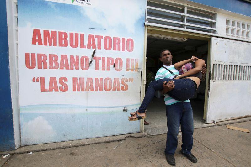 Foto de archivo ilustrativa de un hombre llevando a una mujer tras salir de un centro de salud en San Felix, Venezuela.  Nov 3, 2017.  REUTERS/William Urdaneta