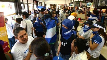 Los opositores que este sábado se manifestaron en Plaza España, fueron obligados a refugiarse en un supermercado ante la represión policial que sufrieron (Cortesía La Prensa)