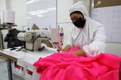 Fotografía fechada el 21 de mayo de 2020 que muestra a las trabajadoras de la empresa de ropa infantil Bareketex mientras fabrican prendas de protección en Bogotá. EFE/Carlos Ortega