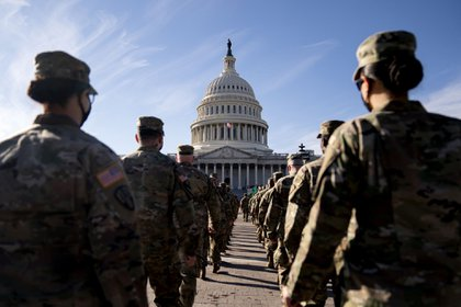 Members of the National Guard march towards the U.S. Capitol in Washington, D.C., U.S., on Friday, Jan. 22, 2021. President Biden warned the nation to prepare for its darkest days in the yearlong pandemic, predicting that as many as 100,000 more Americans will die over the next month as he overhauls the federal coronavirus response and presses Congress for more aid. Photographer: Stefani Reynolds/Bloomberg