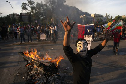 Un grupo de personas se manifestó en Santiago este 26 de octubre, un día después de que más de un millón de personas se manifestó en la capital chilena. (Photo by CLAUDIO REYES / AFP)