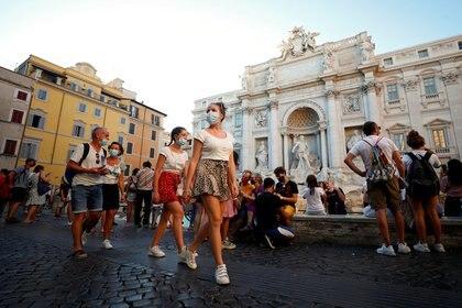 Personas con máscaras faciales caminan frente a la Fontana de Trevi