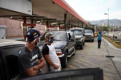 Con mascarillas, los venezolanos hacen fila en una estación de combustible durante la cuarentena nacional en respuesta a la propagación de la enfermedad coronavirus (COVID-19) en Caracas.