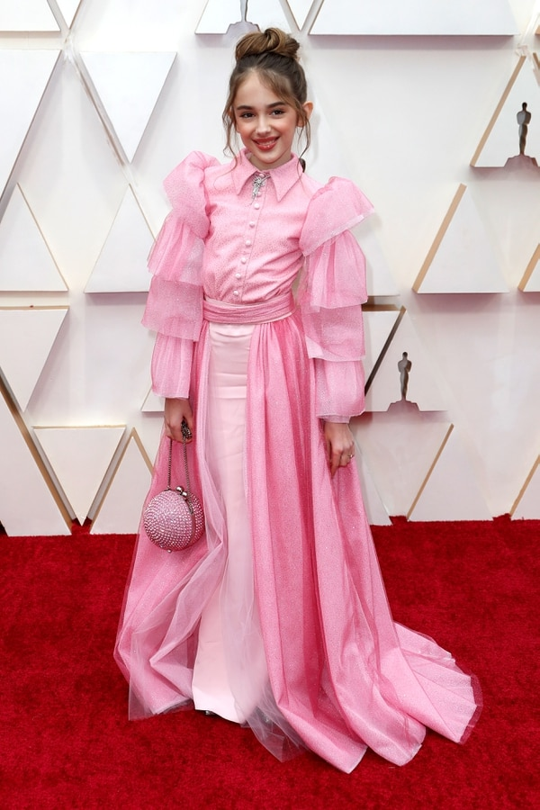 Julia Butters, la más pequeña de la alfombra roja lució un vestido rosado con mangas abullonadas y detalles de glitter. Completó su look con un clutch redondo y colgante de brillantes. El beauty look elegido, un half bun y gloss en los labios