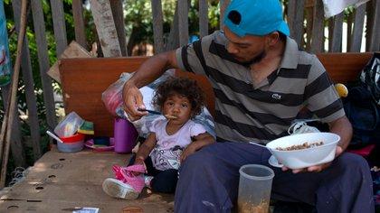 Un venezolano y su hija comen en el lado de una carretera en Boa Vista, estado de Roraima, Brasil (AFP PHOTO / Mauro Pimentel)