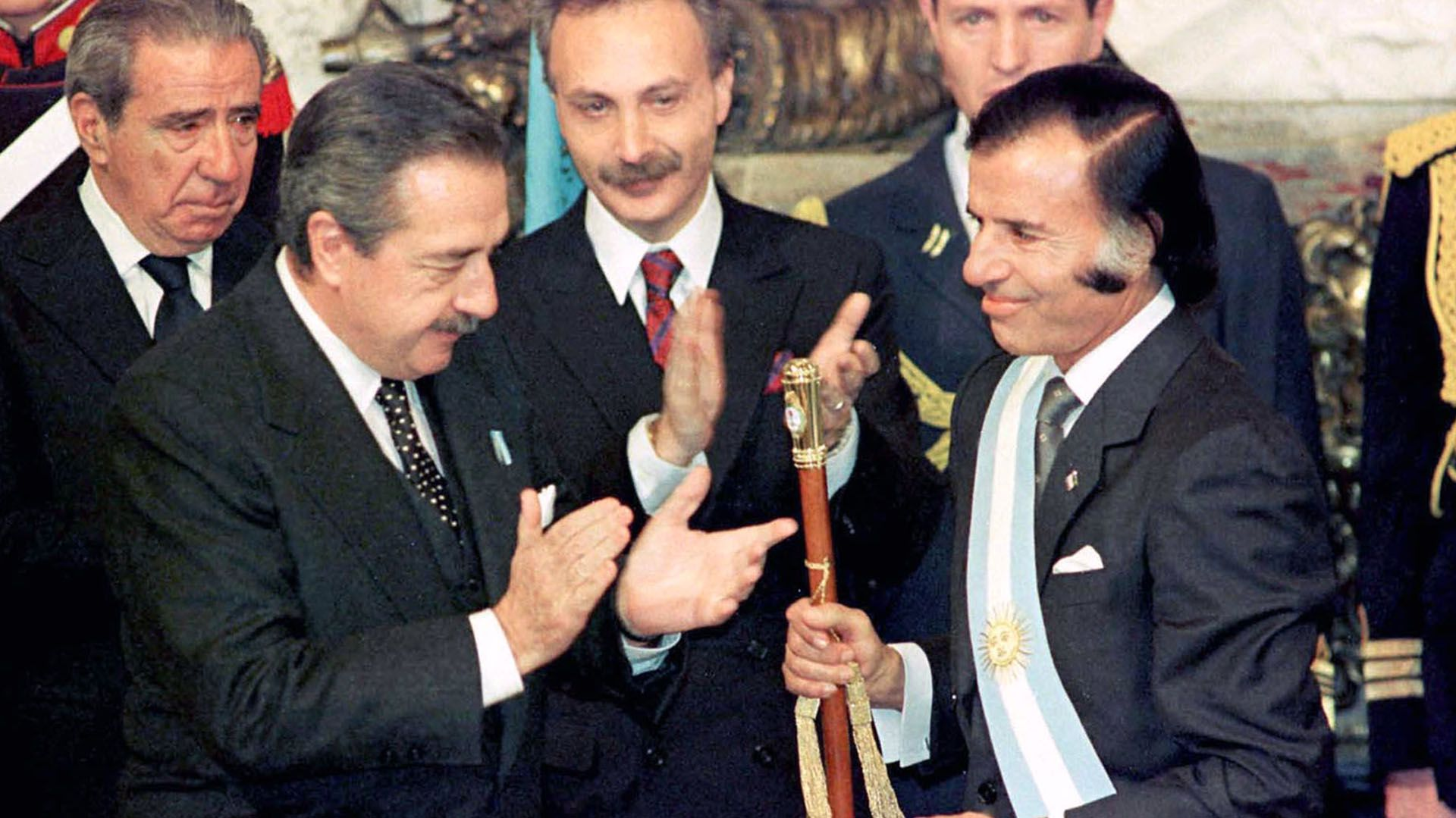 Raúl Alfonsín entrega la banda y el bastón presidencial a Carlos Menem, que llegó antes al gobierno por la crisis institucional que demolió a la administración radical