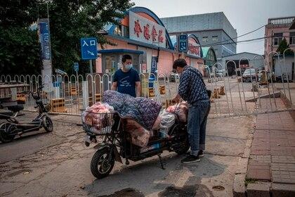 Hombres hacen compras ante el nuevo brote de coronavirus en China