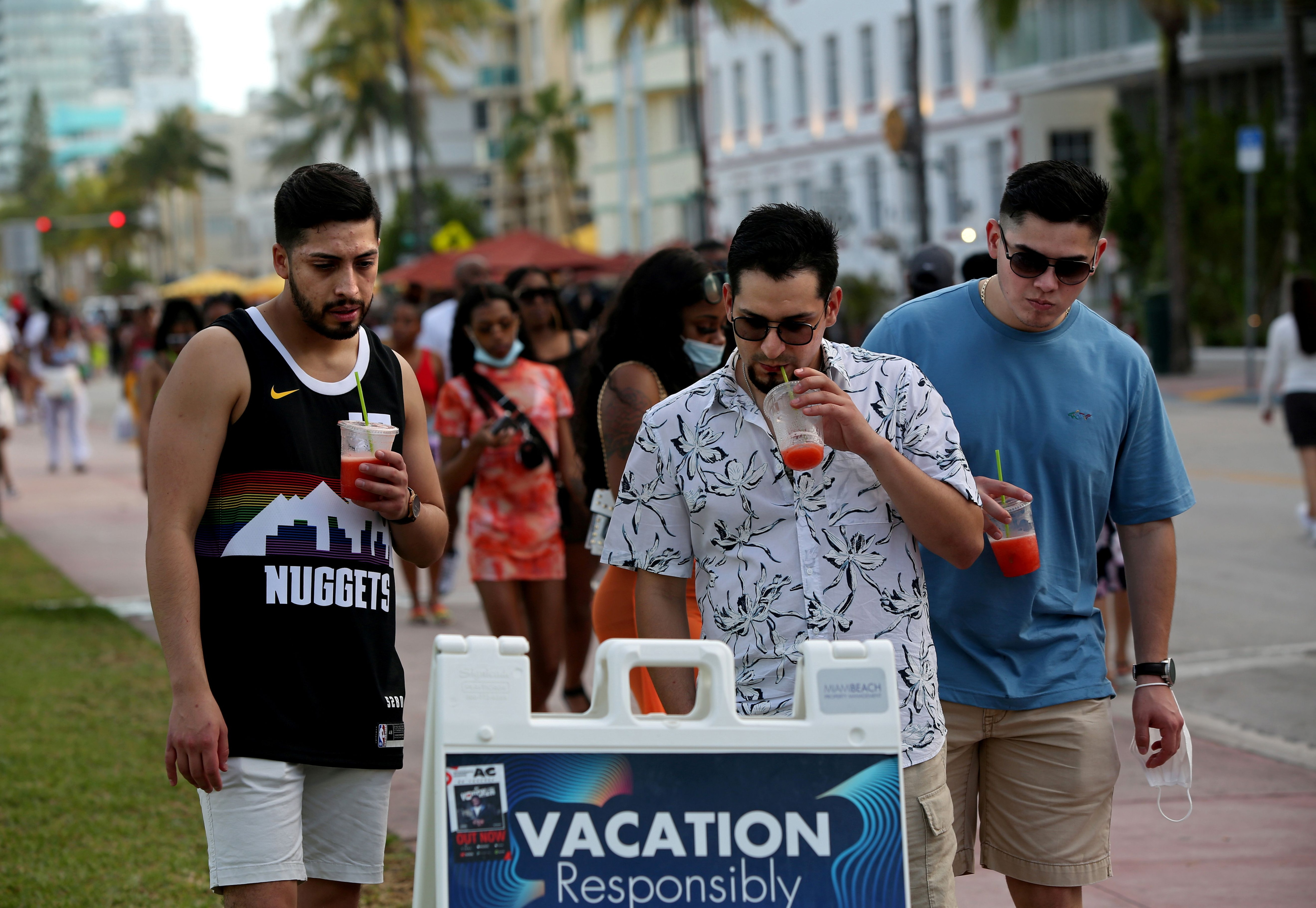 FILE PHOTO: A group of men read public safety precautions while enjoying the bars and restaurants on South Beach during Spring Break amid the coronavirus disease (COVID-19) pandemic, in Miami, Florida, U.S., March 27, 2021.  REUTERS/Yana Paskova/File Photo