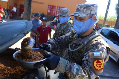 Military staff wearing protective masks serve a ration of food aid, organized by the municipality for a low-income neighborhood, during the mandatory quarantine for coronavirus disease (COVID-19), in Quilmes, on the outskirts of Buenos Aires, Argentina March 23, 2020
